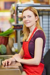 Kassiererin sitzt an Kasse vom Supermarkt
