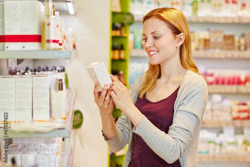 Leinwanddruck Bild Frau hält Produkt in der Drogerie in der Hand