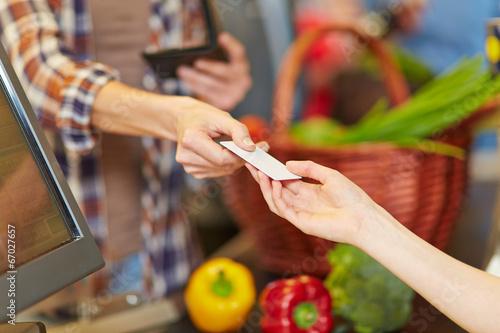 Hand zeigt Kundenkarte an Kasse im Supermarkt - 67027657