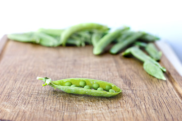 Fresh green peas pod on the wood background