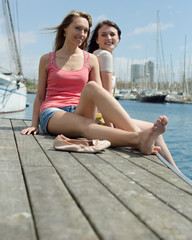 Two girls students resting on the sea berth