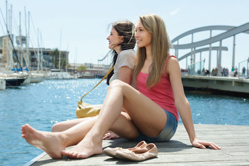 Two female students in shorts resting on the berth