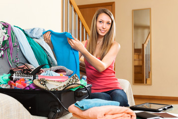Woman sitting on couch near opened suitcase