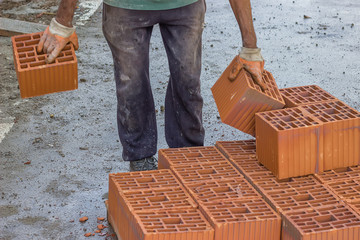 builder worker carrying hollow clay block