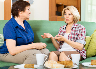 Two sad mature women chating on couch