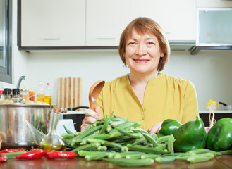 Smiling mature woman cooking okra