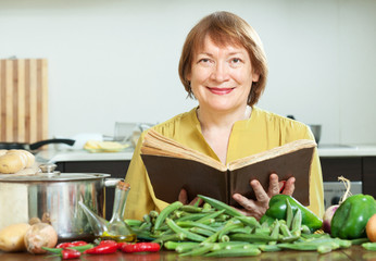 mature woman cooking   with  cookery book in  kitchen
