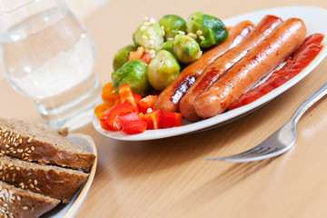 grilled sausages with broccoli on white plate