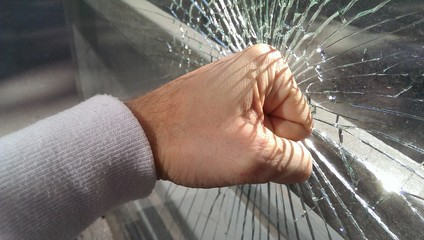 Male fist and broken glass with cracks