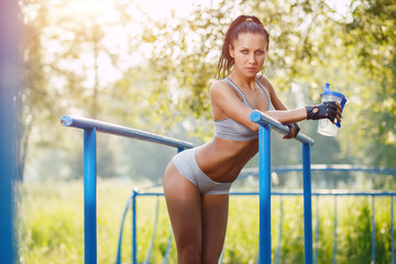 fitness girl relax after workout on bars with bottle of water