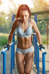 fitness woman doing exercise on parallel bars outdoor