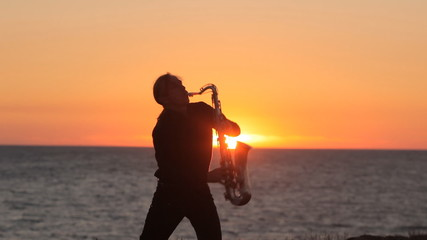 The silhouette of a musician playing saxophone on the seacoast