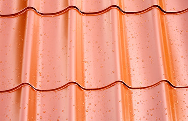 Fagment of red metal roof with water drops as background