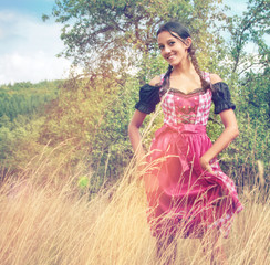Young woman in dirndl walking alone in the field