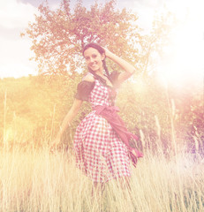 Young woman wearing dirndl posing in the field