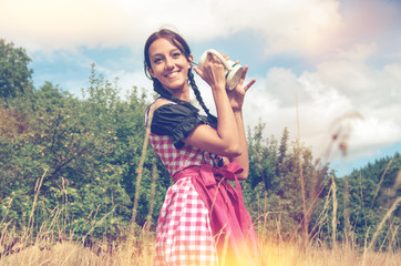 Girl in traditional bavarian dirndl holds beer mug