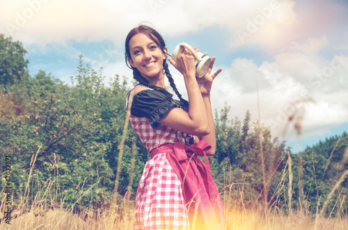 canvas print picture Girl in traditional bavarian dirndl holds beer mug
