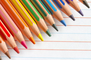 Colorful pencils crayons on white paper abstract background