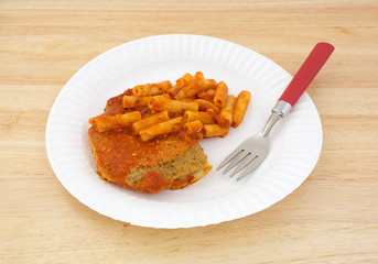 TV dinner of breaded chicken and pasta on paper plate