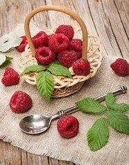 Small basket with fresh raspberries on wooden background