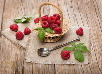 Sweet raspberries in basket  on the wooden table
