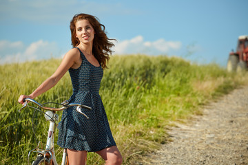 Woman riding bicycle in country field