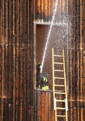 Firefighter with hydrant in action when switching off a fire