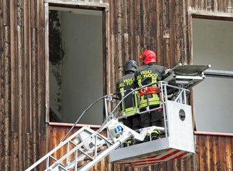 Italian firefighters while rising with the mobile platform to fr
