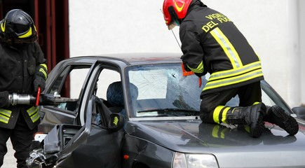 firefighters in action while they open the car after the acciden