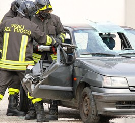 brave firefighters with pneumatic shears cut the sheets of car