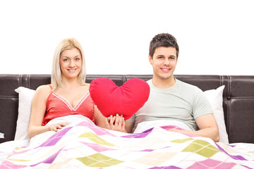 Young couple lying in bed and holding a red heart