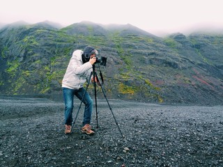 Photographer with a tripod, in the mountains of Iceland