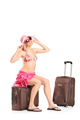 Happy female tourist sitting on her luggage