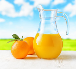 Jug of orange juice on nature background