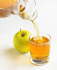 Apple juice pouring from jug into a glass