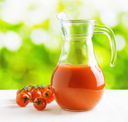 Jug of tomato juice on nature background. Half full pitcher