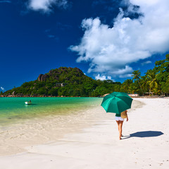 Woman with umbrella at beautiful beach