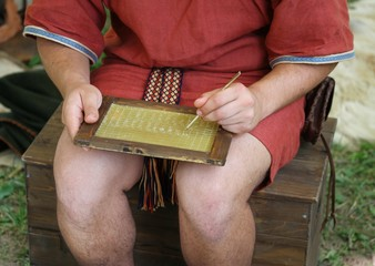 young SCRIBE writes on a wax Tablet