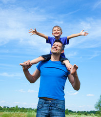 Happy father with son outdoors against sky