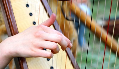 hand while plucking the strings of a harp