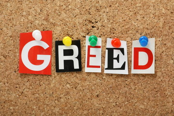 The word Greed on a cork notice board