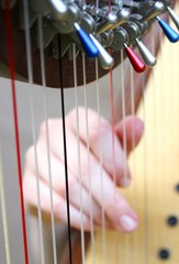 female hand while plucking the strings of a harp 1