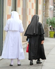 nun with black suit and white dress walking in town
