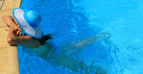 Young lady with white blue hat by the poolside