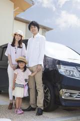 車の前に立つ家族
