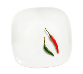 Green and red hot peppers on a plate isolated over white
