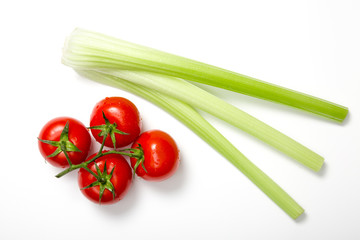 Top view of bunch of fresh tomatoes and celery sticks