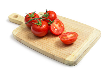 Fresh tomatoes on wooden chopping board