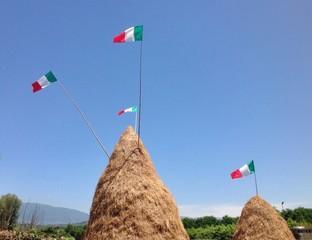 Covoni di fieno con bandiere italiane