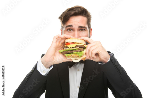 canvas print picture junger Geschäftsmann isst  großen Burger